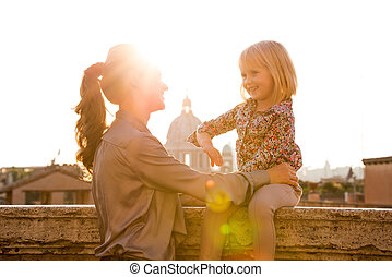 Mother holding daughter sitting on ledge in Rome - At...
