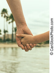 Mother holding hand of her daughter.
