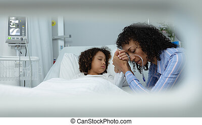 Side view of sad mixed race mother holding hands of her son in the ward at hospital