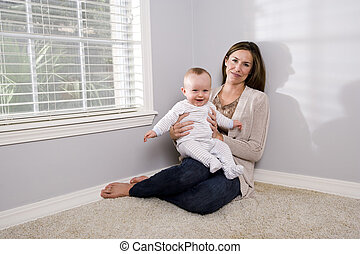 Mother holding happy six month old baby