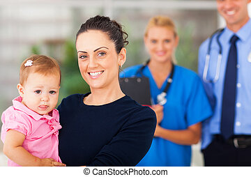 mother holding her baby girl in doctors office