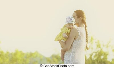 Mother holding her baby girl on summer field in the evening