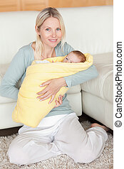 Mother holding her baby that is wrapped into a cover