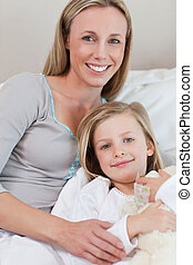 Mother holding her daughter on the bed