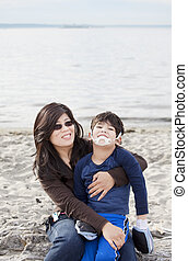 Mother holding her disabled son on the beach