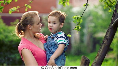 Mother holding her son and they talking outdoor