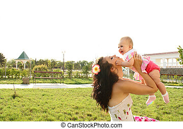 Mother holding sweet baby, over park outdoors