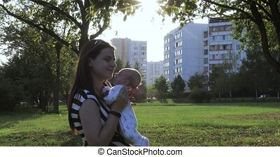 Mother holding the infant on sunset