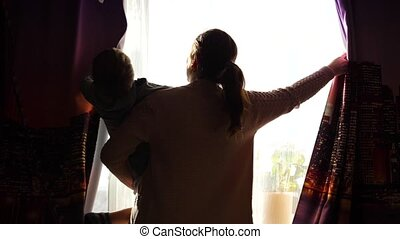 Mother holds a child in the morning near the window. Early in the morning they open the curtains, the sun's rays pass through the window. sunrise