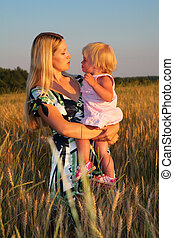 Mother holds child on hands in wheat field