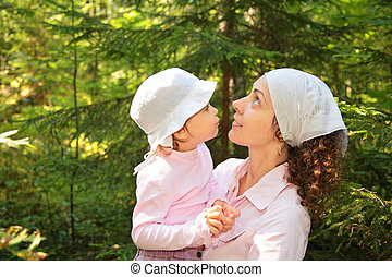 mother holds daughter in hands in woods