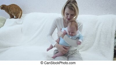 Mother holds her baby while sitting on the sofa.