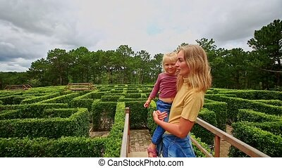 Mother Holds in Arms Little Girl Watch Labyrinth from Bridge...