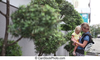 mother holds little blonde daughter in  arms near decorated bonsai trees