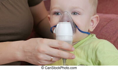 Mother holds the mask on the baby inhaler and breathes the ...