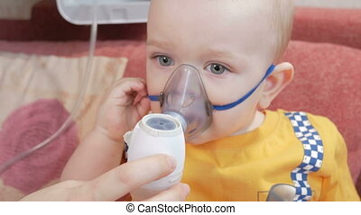 Mother holds the mask on the baby inhaler and breathes the medicine at home. Treats inflammation of the airways via nebulizer. Preventing asthma and cough