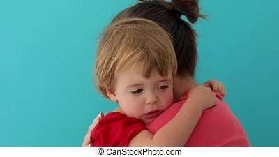 Mother hugging adorable little child - Side view of young...