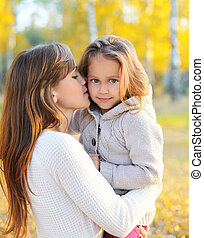 Mother hugging and kissing child in autumn day