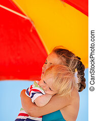 Mother hugging baby on beach under umbrella