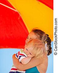 Mother hugging baby on beach under umbrella