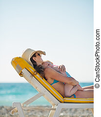 Mother hugging baby while laying on sunbed on beach