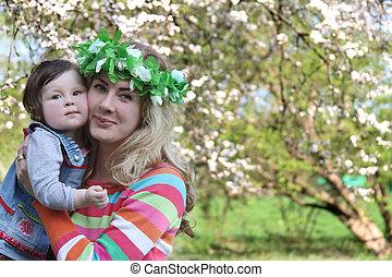 Mother hugging cheek-to-cheek baby girl
