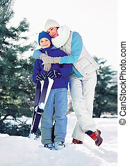 Mother hugging child with ski in winter forest