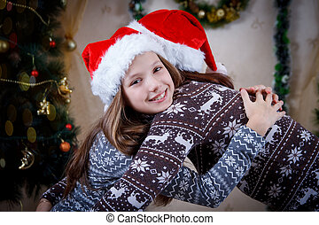 Mother hugging daughter under Christmas tree