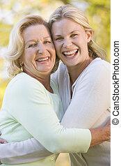 Mother hugging grown up daughter