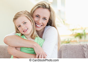 Mother hugging her daughter on sofa