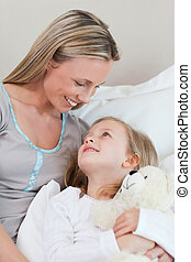 Mother hugging her daughter on the bed