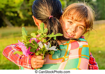Mother hugging her daughter with flowers