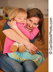 Mother hugs her cute little daughter