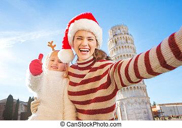 Mother in Christmas hat taking selfie with daughter in Pisa