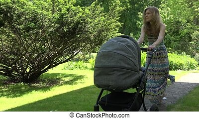 Mother in dress try to send baby to sleep in stroller in garden. 4K