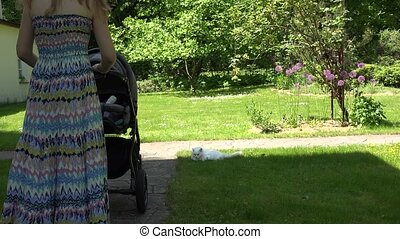 Mother in dress try to send baby to sleep in stroller in garden.