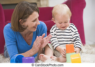 Mother in living room playing with baby smiling
