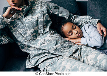 mother in military uniform with sleeping daughter