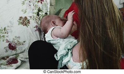 Mother in red shirt breastfeeding little baby on sofa. Motherhood. Healthcare.