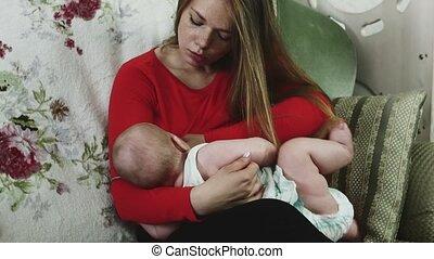 Mother in red shirt breastfeeding little baby on sofa. Motherhood. Immunity.
