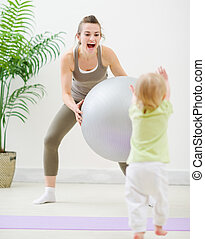 Mother in sportswear playing with baby at gym