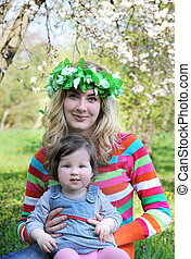 Mother in wreath and baby girl under spring trees