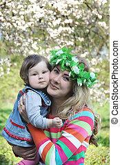Mother in wreath hugging baby girl