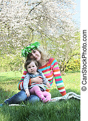 Mother in wreath sitting with baby girl under spring tree