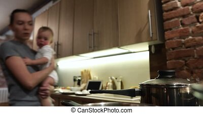 Mother is cooking dish is spoiled baby in arms - Nanny with...