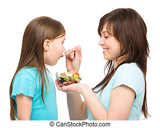 Mother is feeding her daughter with fruit salad