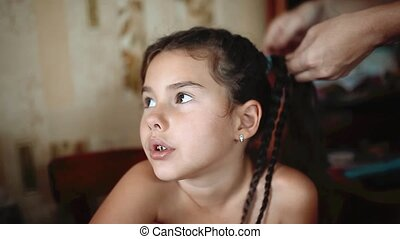 Mother is making of braids on little daughters head....