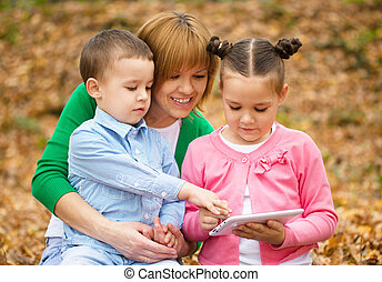 Mother is reading book with her daughter and son