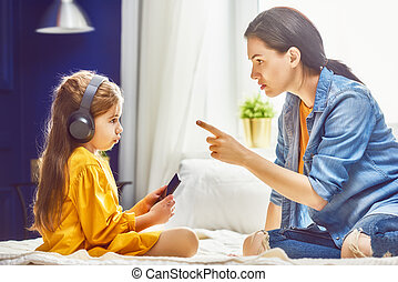 Mother is scolding her child girl playing on phone. Family...