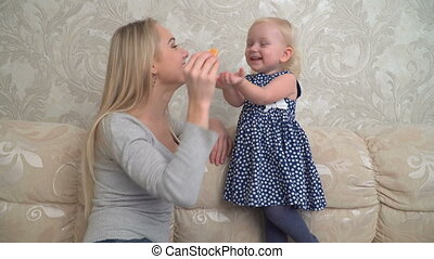 Mother is tenderly playing with her daughter on the sofa